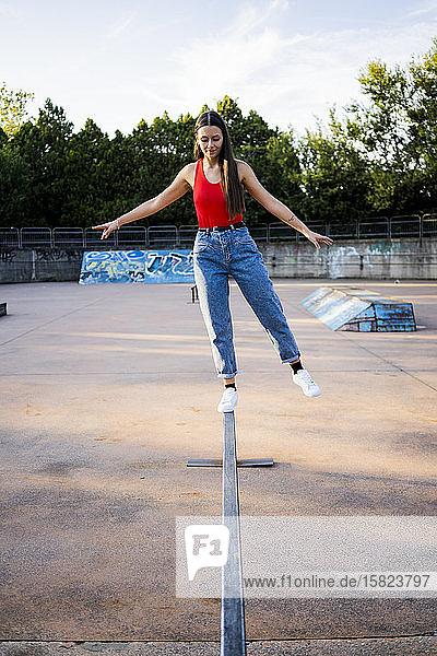 Junge Frau balanciert auf einem Geländer im Skatepark