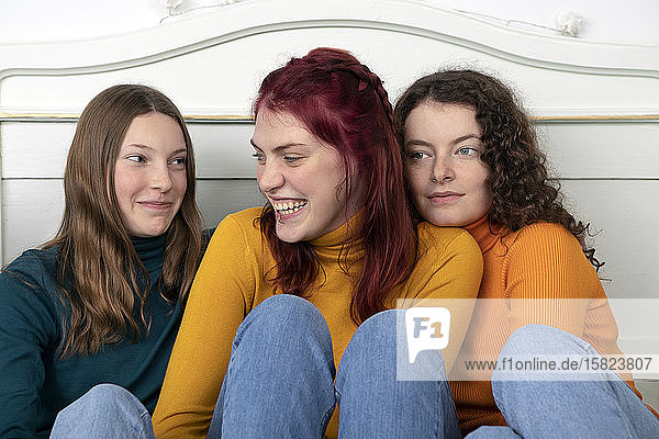 Portrait of three happy sisters sitting together on bed