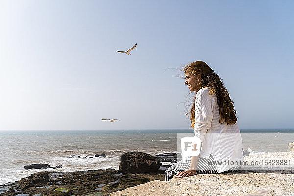 Junge Frau genießt Sonnenlicht in Meeresnähe  Essaouira  Marokko