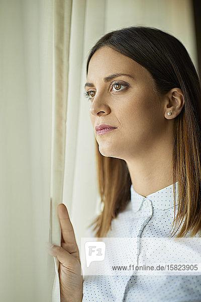 Porträt einer seriösen Geschäftsfrau  die aus dem Fenster schaut
