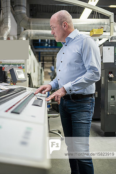 Mann  der eine Maschine in einer Fabrik bedient
