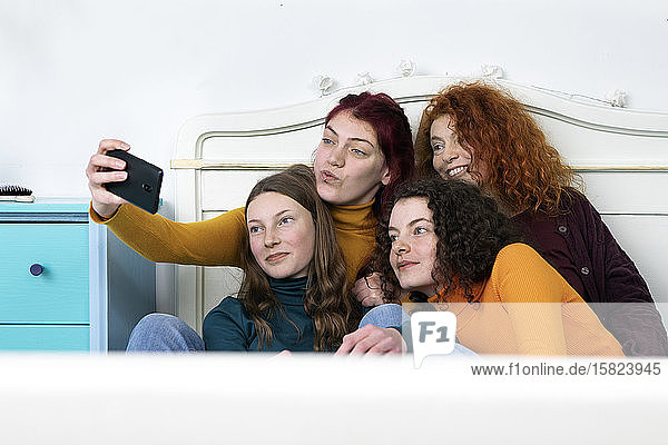 Mother and her three daughters sitting together on bed taking selfie with smartphone