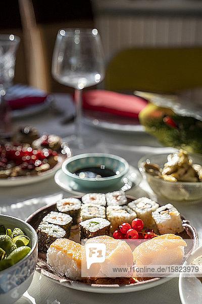 Spanien  Teller mit verzehrfertigem Sushi auf gedecktem Esstisch