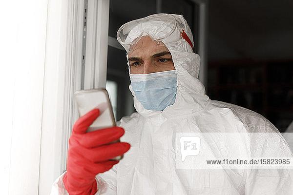 Mann in Schutzkleidung  benutzt Smartphone