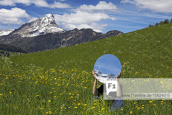 Woman sitting in meadow  hiding behind mirror  reflecting the mountains of Val Badia  Alto Adige  Italy