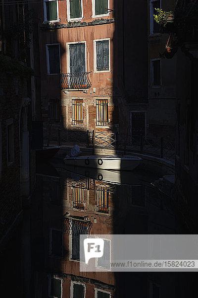 Italien  Venedig  Haus beleuchtet von den letzten Strahlen der untergehenden Sonne  die sich auf der Oberfläche des Kanals reflektieren