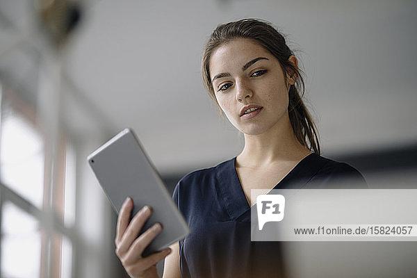 Porträt einer jungen Geschäftsfrau mit digitalem Tablett im Büro