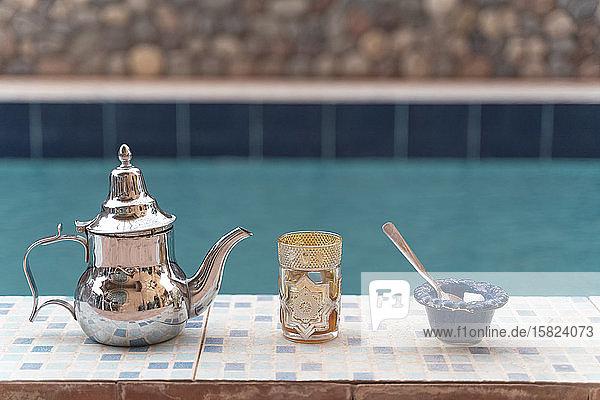 Silberne Teekanne  Teeglas und Zuckerdose am Beckenrand