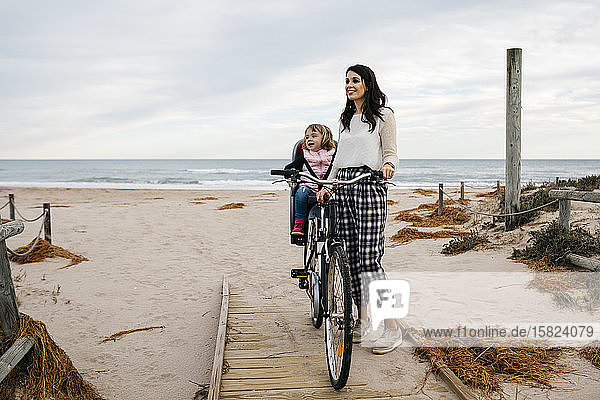 Woman with bicycle on a boardwalk in the dunes with daughter in child's seat