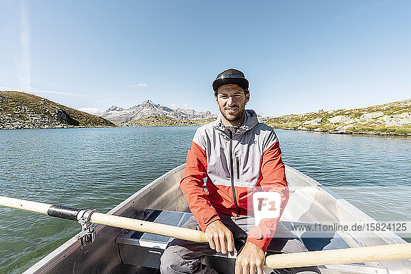 Young smiling man in a rowing boat  Lake Suretta  Graubuenden  Switzerland