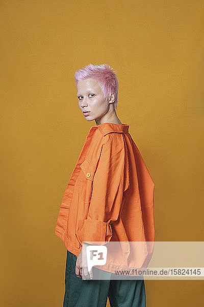 Portrait of young woman with short pink hair wearing orange jacket in front of yellow background