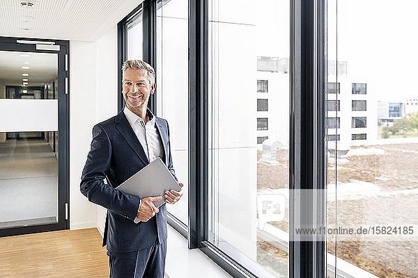 Geschäftsmann mit Laptop vor dem Fenster des Bürogebäudes