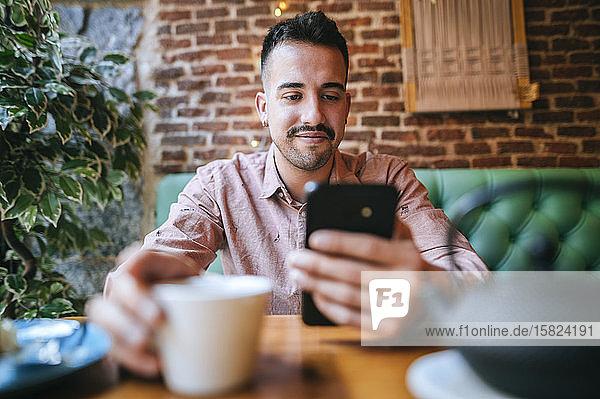 Porträt eines lächelnden Mannes in einem Cafe  der auf sein Handy schaut