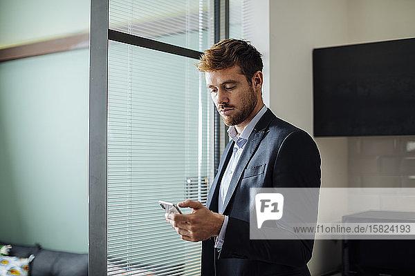 Junger Geschäftsmann benutzt Mobiltelefon zu Hause Junger Geschäftsmann benutzt Mobiltelefon zu Hause