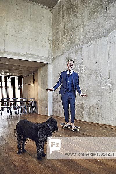 Leitender Geschäftsmann beim Skateboarden in seinem Büro  Hund schaut zu