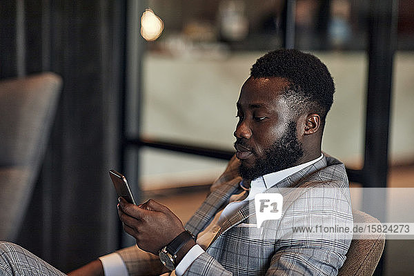 Businessman sitting in armchair using smartphone