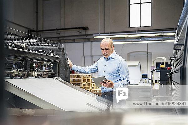 Geschäftsmann mit Tablettenprüfgerät in einer Fabrik