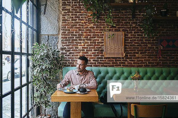 Mann in einem Café  der Notizen macht