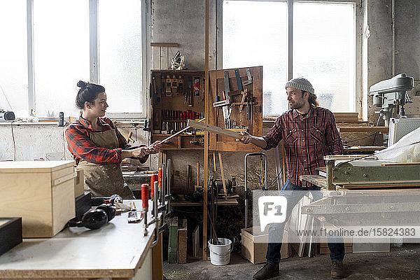 Verspielte Handwerkerin und Handwerker kämpfen in ihrer Werkstatt