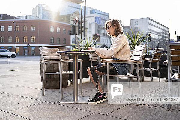 Junge Frau mit Beinprothese sitzt mit Laptop in einem Straßencafé in der Stadt Junge Frau mit Beinprothese sitzt mit Laptop in einem Straßencafé in der Stadt