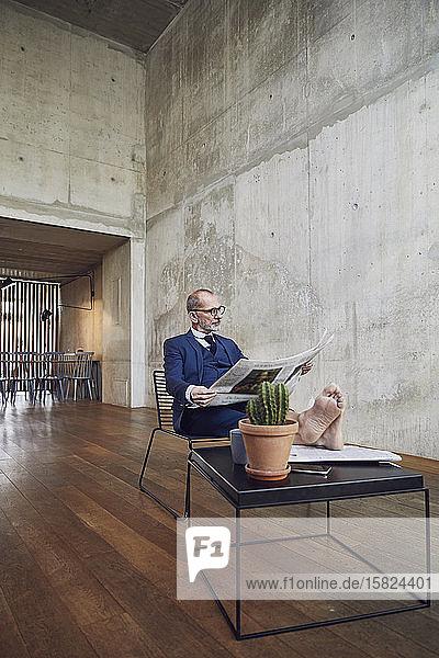 Leitender Geschäftsmann sitzt in seinem Büro und liest Zeitung