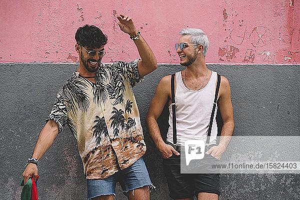 Schwules lachendes Paar vor einer rosa-grauen Wand