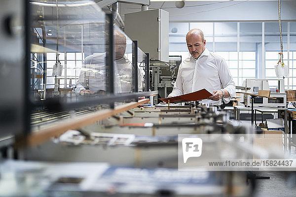 Geschäftsmann in einer Druckerei bei der Produktkontrolle