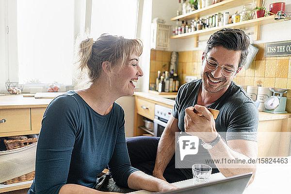 Glückliches Paar beim Online-Einkauf in der heimischen Küche