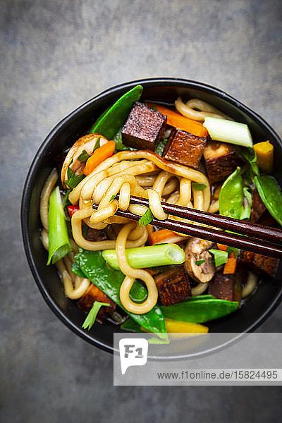 Ein Paar Stäbchen und eine Schüssel fertige Misosuppe mit Udon-Nudeln  Tofu  Zuckerschoten  Paprika  Karotten  Mu-err-Pilzen  Frühlingszwiebeln und Koriander
