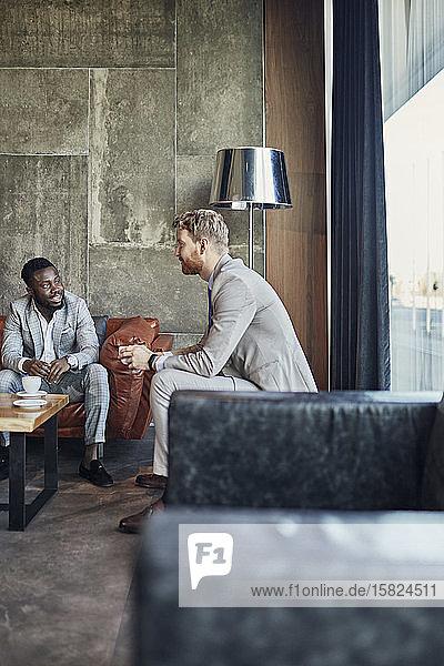 Two businessmen having a coffee break in hotel lobby