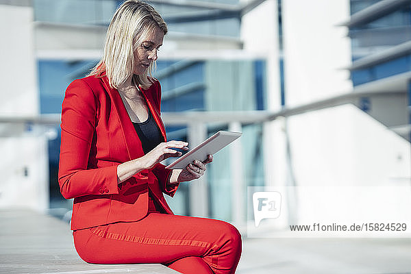 Blond businesswoman wearing red suit and using digital tablet at an office building