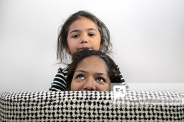Portrait of little girl and her mother hiding behind back rest of lounge chair
