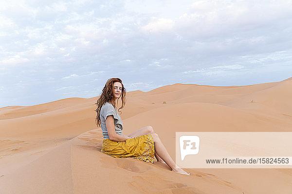 Porträt einer rothaarigen jungen Frau  die in einer Sanddüne in der Wüste Sahara sitzt  Merzouga  Marokko