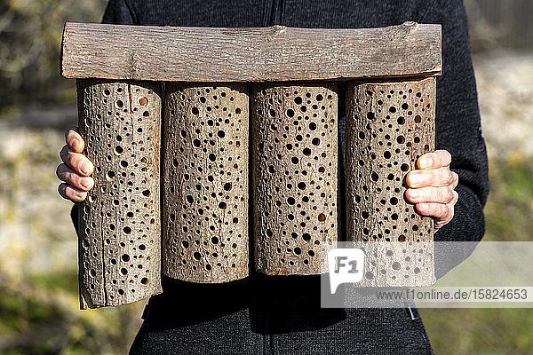 Mann mit selbstgebautem Bienenhotel aus Holz
