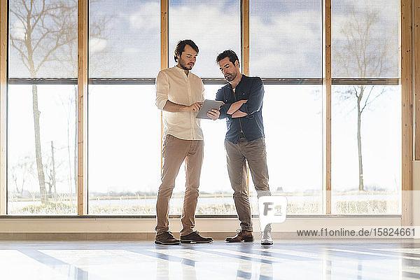 Zwei Geschäftsleute mit Tablett sprechen am Fenster im hölzernen Großraumbüro
