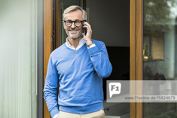 Smiling senior man with grey hair standing in front of his modern design home talking on the phone
