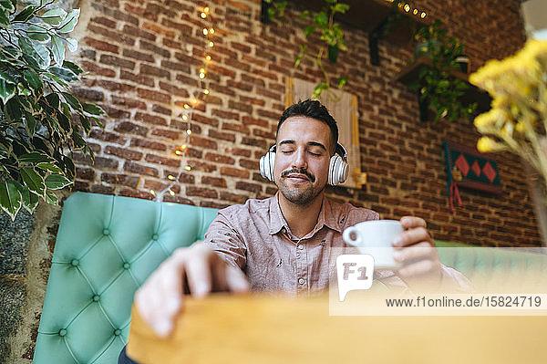 Lächelnder Mann mit geschlossenen Augen in einem Café  der mit Kopfhörern Musik hört