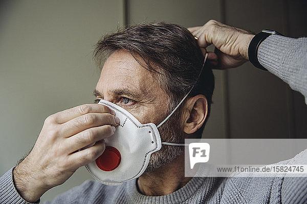 Mature man putting on protective mask