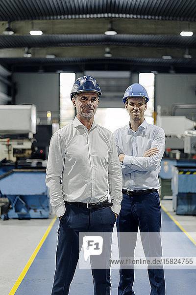 Porträt von zwei selbstbewussten Männern mit Schutzhelmen in einer Fabrik
