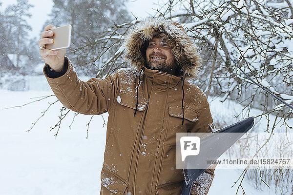 Porträt eines lächelnden Mannes mit Schneeschaufel  der sich mit dem Handy selbstständig macht