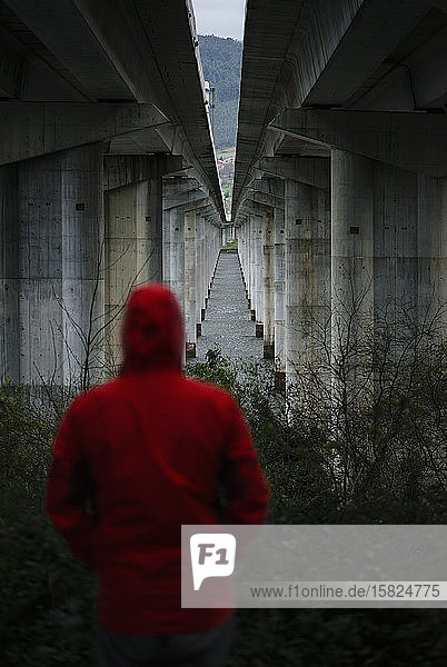 Man at a highway bridge in abandoned environment