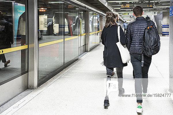 Rückansicht einer jungen Frau mit Beinprothese und eines gehenden Mannes auf dem Bahnsteig einer U-Bahn-Station