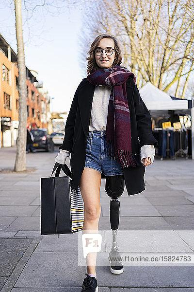 Porträt einer selbstbewussten jungen Frau mit Beinprothese beim Spaziergang in der Stadt