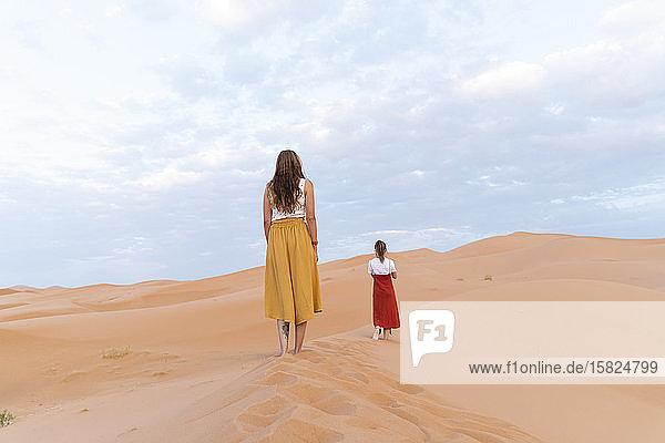 Rückansicht von zwei jungen Frauen auf einer Sanddüne in der Wüste Sahara  Merzouga  Marokko