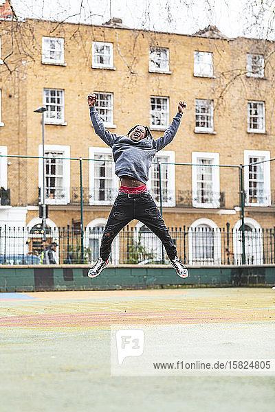 Junger glücklicher Mann springt und lacht in der Stadt