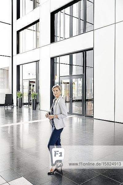Erfolgreiche Geschäftsfrau steht in der Eingangshalle eines Bürogebäudes