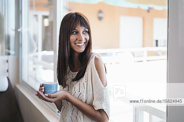 Porträt einer lächelnden jungen Frau mit Kaffeetasse nahe am Fenster zu Hause