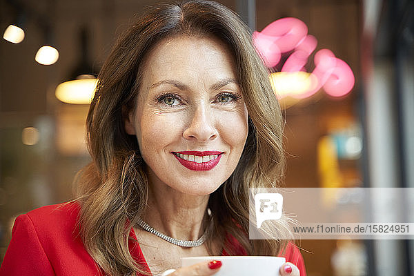 Portrait of smiling mature woman with cup of coffee in a cafe