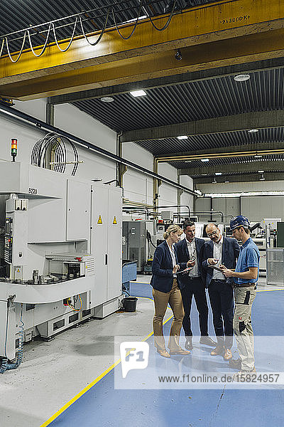 Geschäftsleute und Arbeiter im Gespräch in einer Fabrik