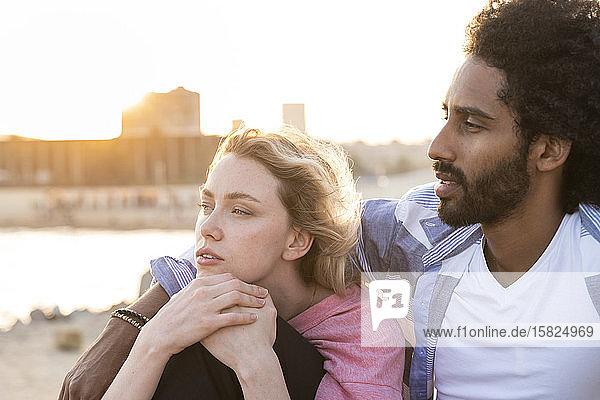 Porträt eines jungen Paares im Freien bei Sonnenuntergang